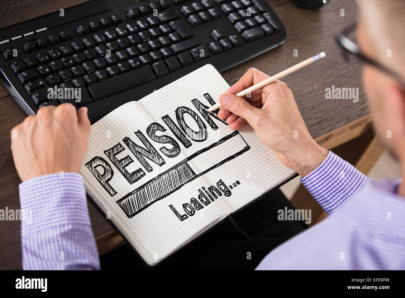 Close-up Of A Businessperson Drawing Pension Concept On Checkered Notebook In Office - Stock Image
