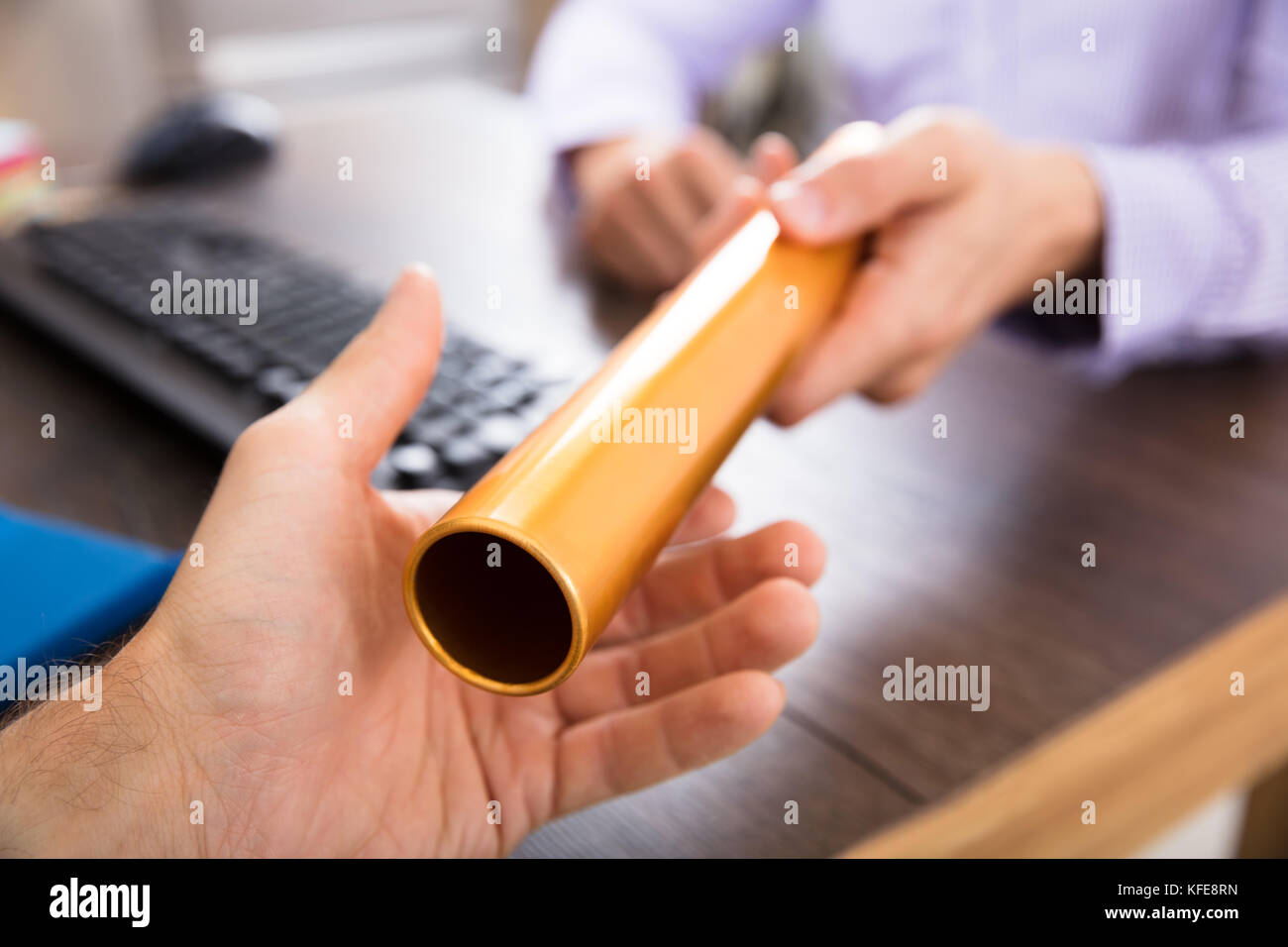 Close-up Of A Person's Hand Passing Golden Relay Baton To Businessman - Stock Image