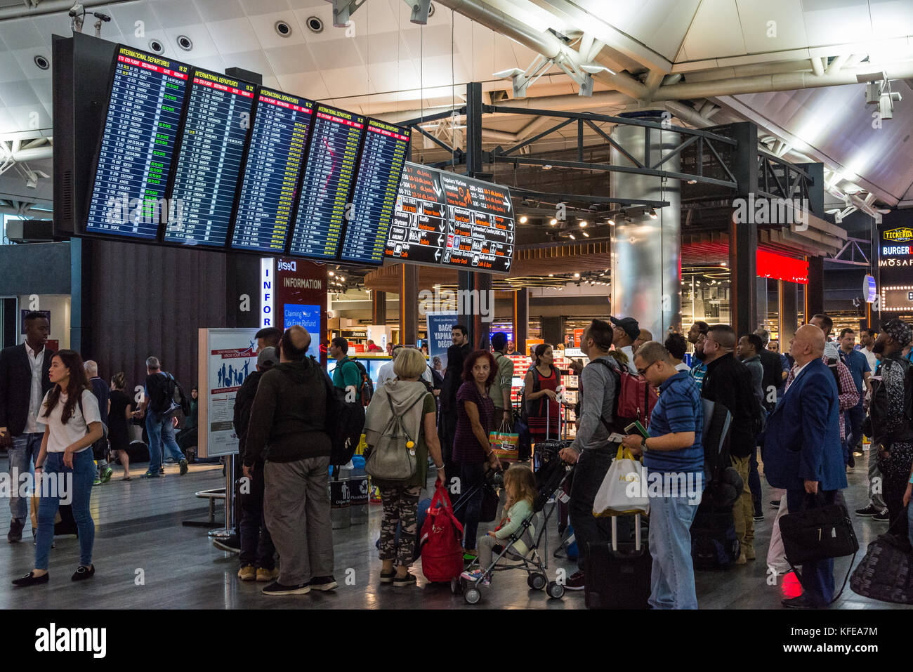 Passengers check the schedule board at Istanbul Airport, Turkey. - Stock Image