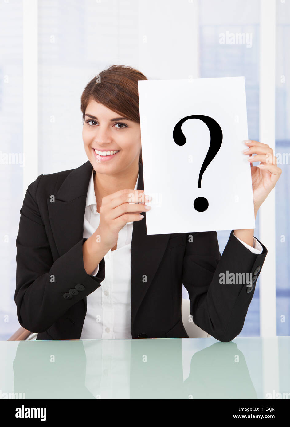 Businesswoman holding paper with question mark in front of face at desk in office - Stock Image