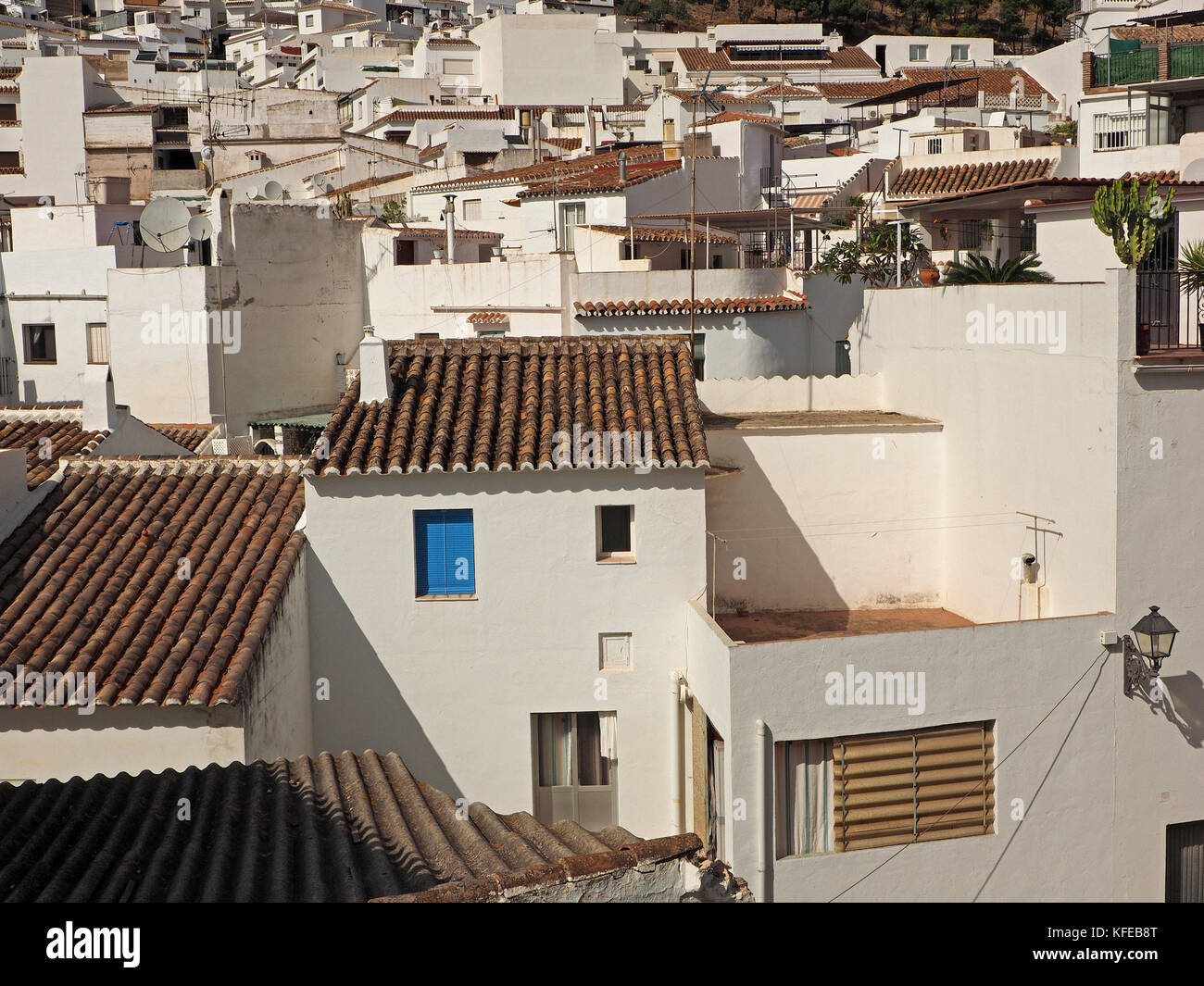 a blue shuttered window stands out from the white walls and brown rooftops of buildings in the picturesque historic - Stock Image