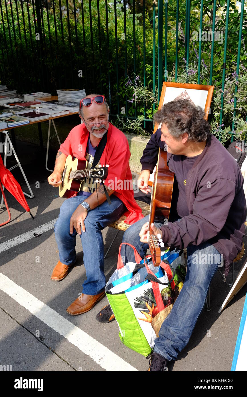 2 stall holders play guitar at the Marche Aux Puces flea market in Porte de Vanves in Paris on a Sunday morning - Stock Image