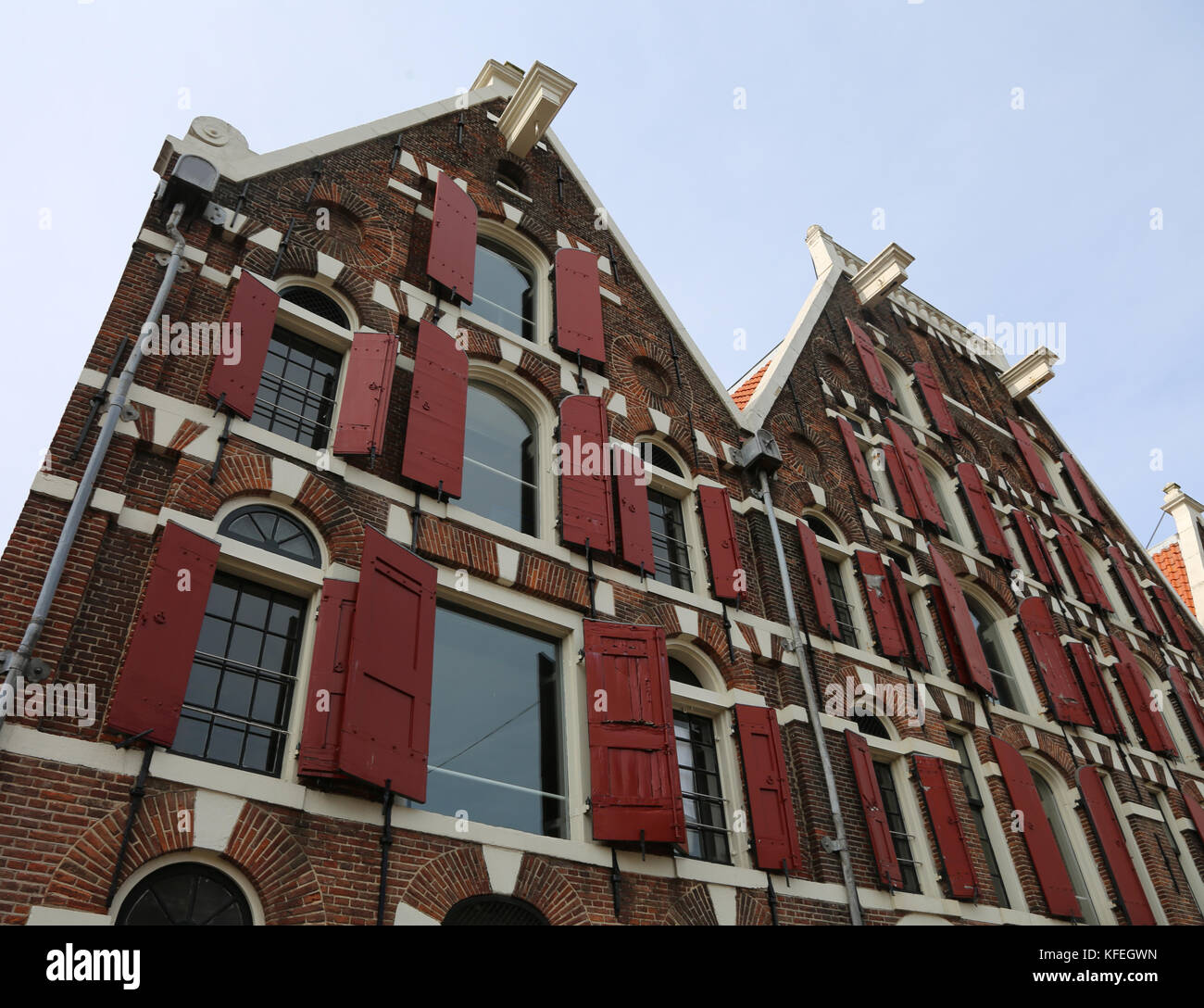 facade of Dutch house facades and under the roof the protruding hook to lift the furniture during removals - Stock Image