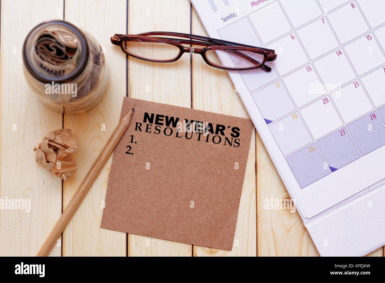 new years resolutions concept with eye glassescalendar pencilcrumpled paper and a