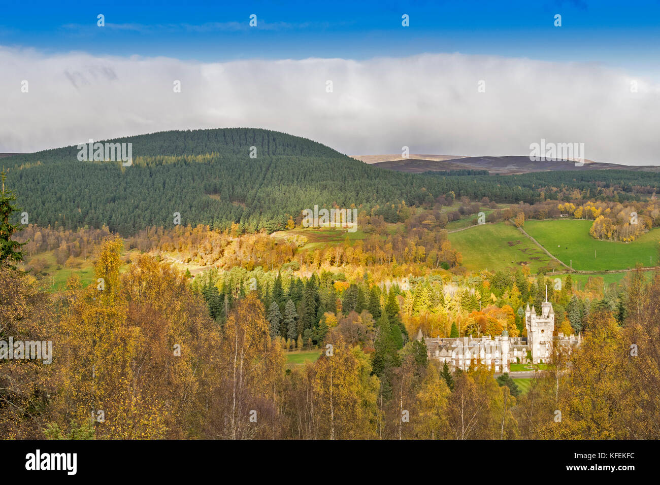 BALMORAL CASTLE ROYAL DEESIDE ABERDEENSHIRE SCOTLAND SUNLIGHT ON THE CASTLE AND HILLS AND BIRCH TREES WITH AUTUMN - Stock Image