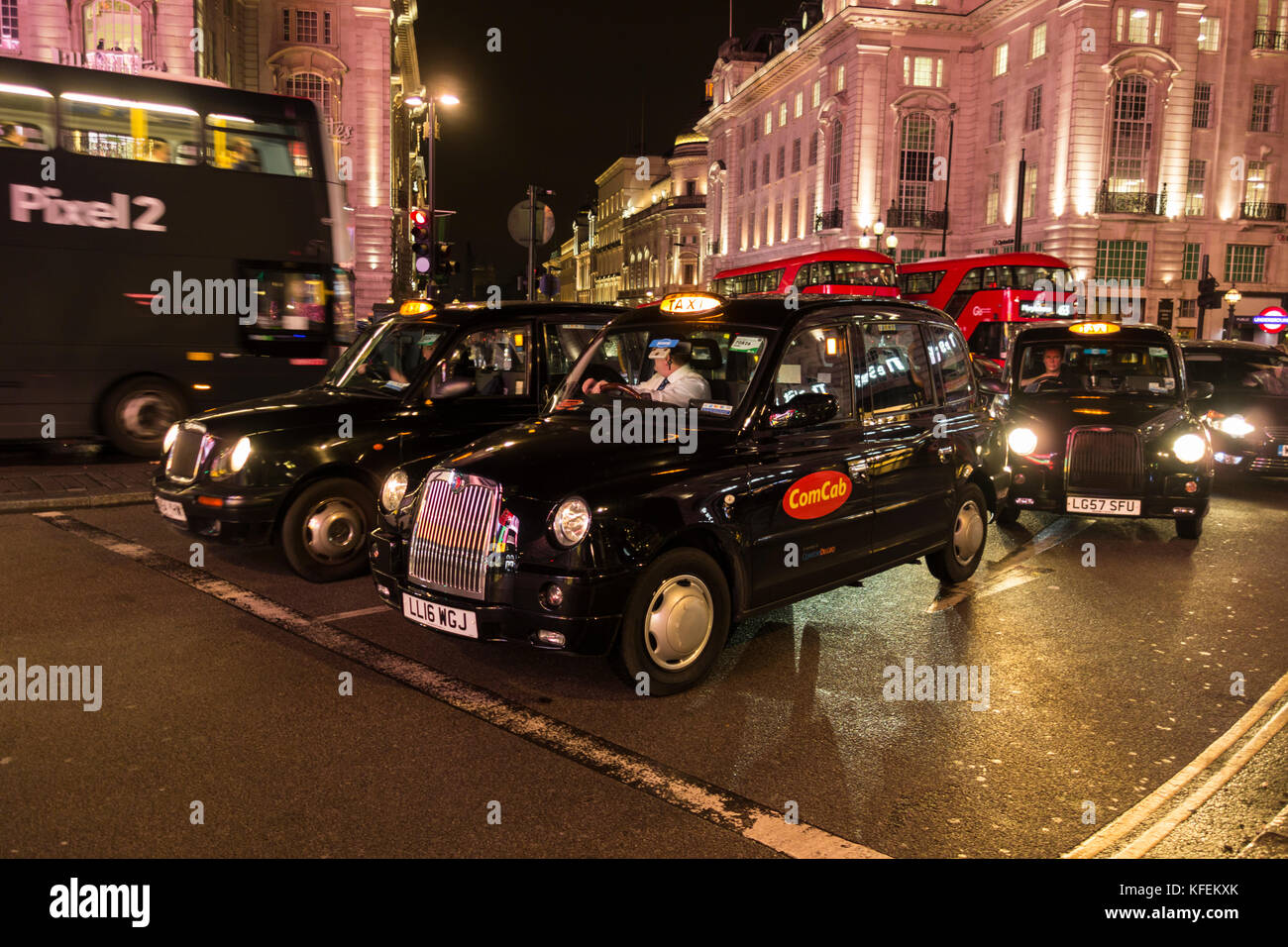 Black London taxicabs waiting for the lights to change on Piccadilly Circus, London, UK - Stock Image