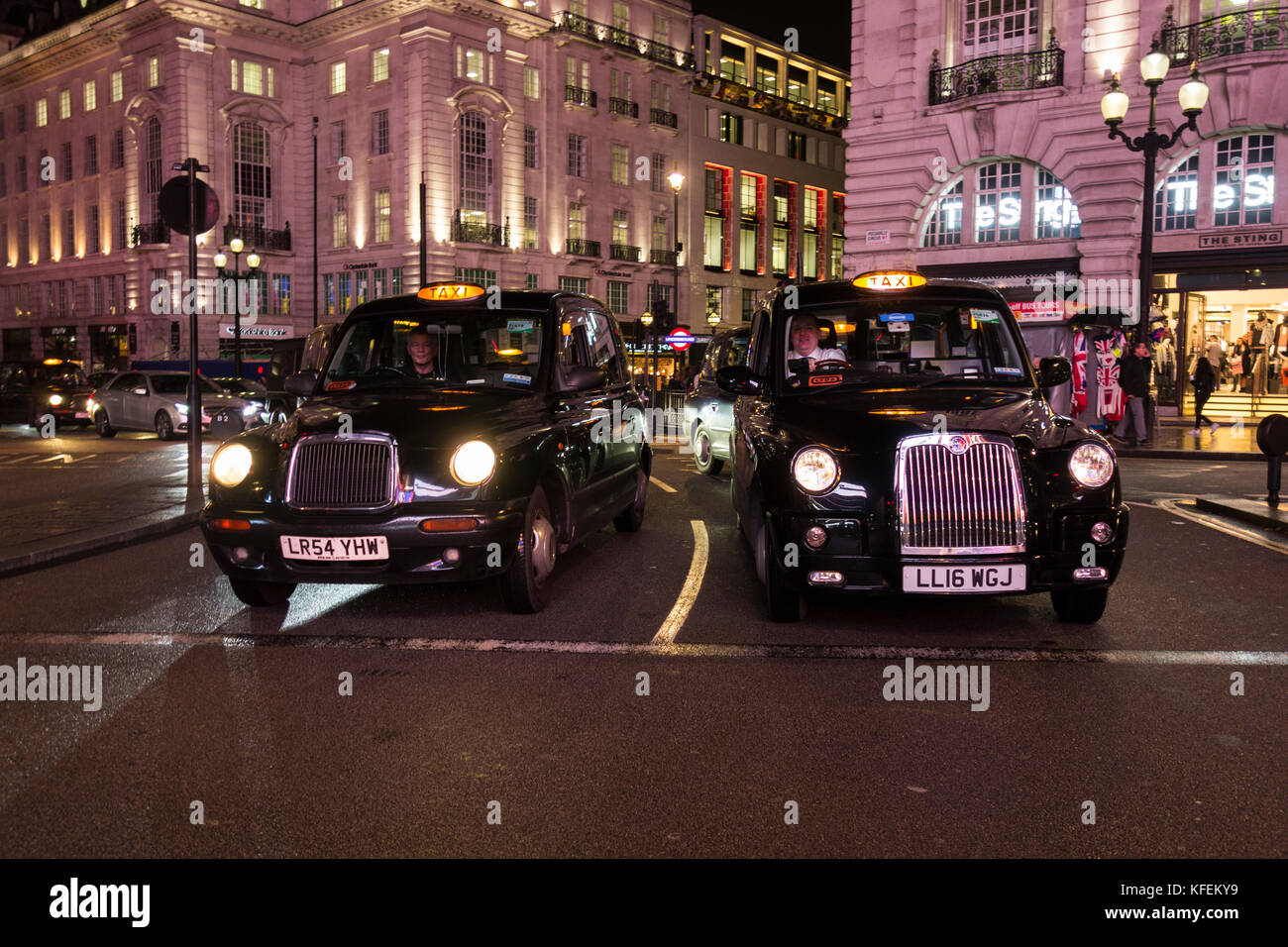 Black London taxicabs waiting for the lights to change on Piccadilly Circus, London, UK Stock Photo