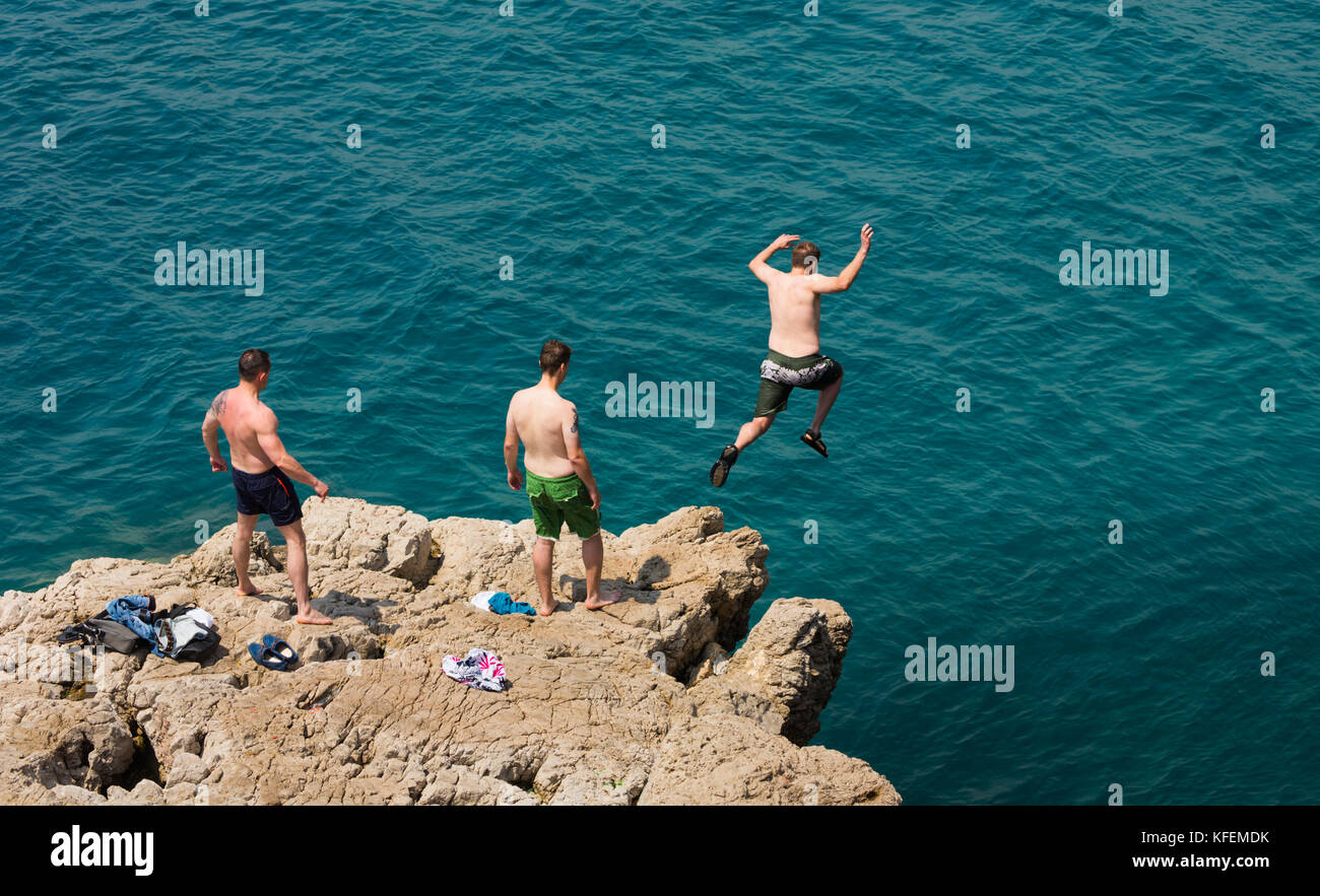 Nice, French Riviera, Cote d'Azur, France.  Bather jumping from rock into sea at Pointe de Rauba-Capeu. - Stock Image