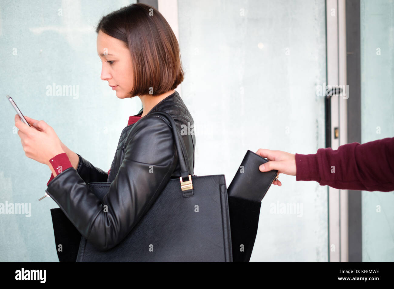 Thief picking the wallet from the bag of a careless girl - Stock Image