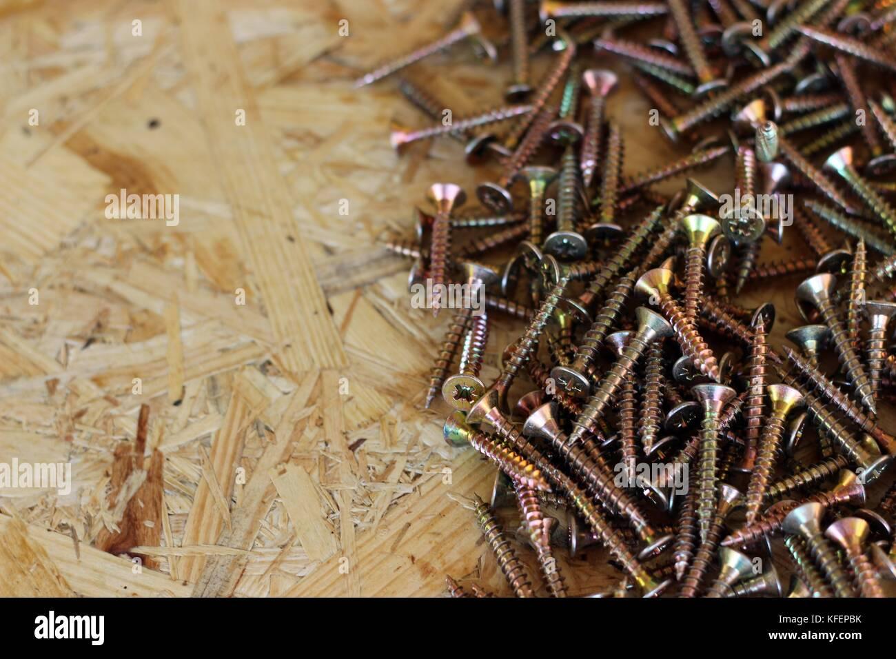 wood screw, brown background, carpenter tool - Stock Image