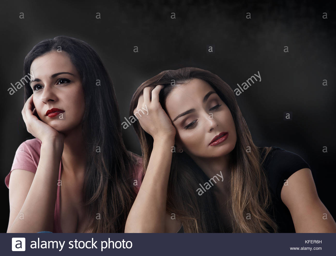 Two sad worrying women, holding head on hands - Stock Image