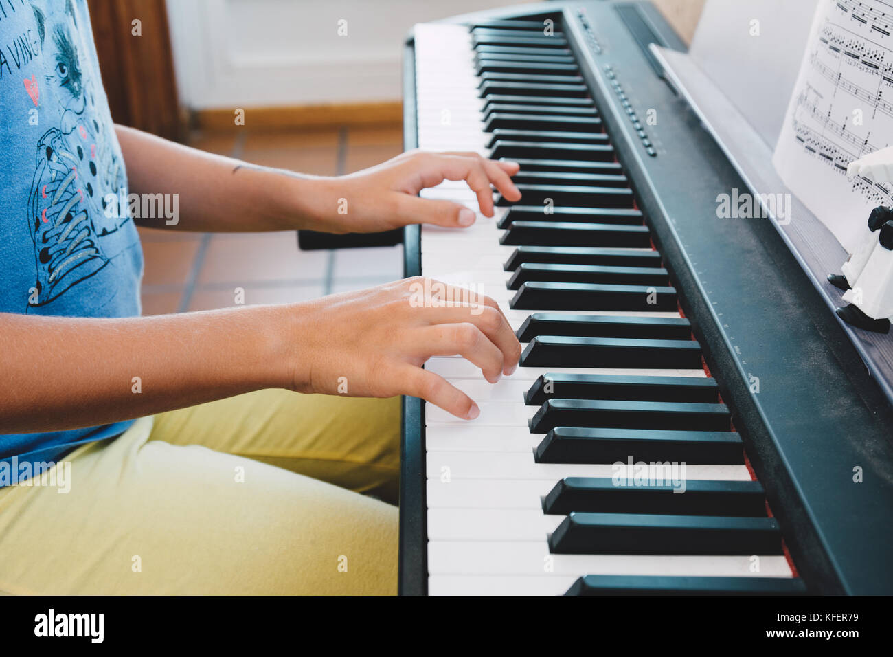 9-year-old girl playing the electric piano in front of the score book - Stock Image