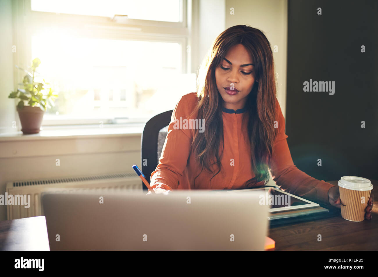 Young African female entrepreneur sitting at a desk in her home office writing down notes while drinking coffee - Stock Image