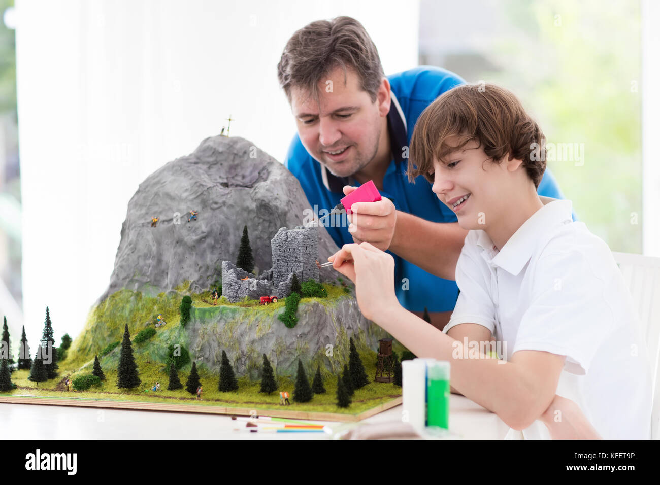 Father and son work on model building school project. Kids and parent build miniature scale model mountain for geography - Stock Image