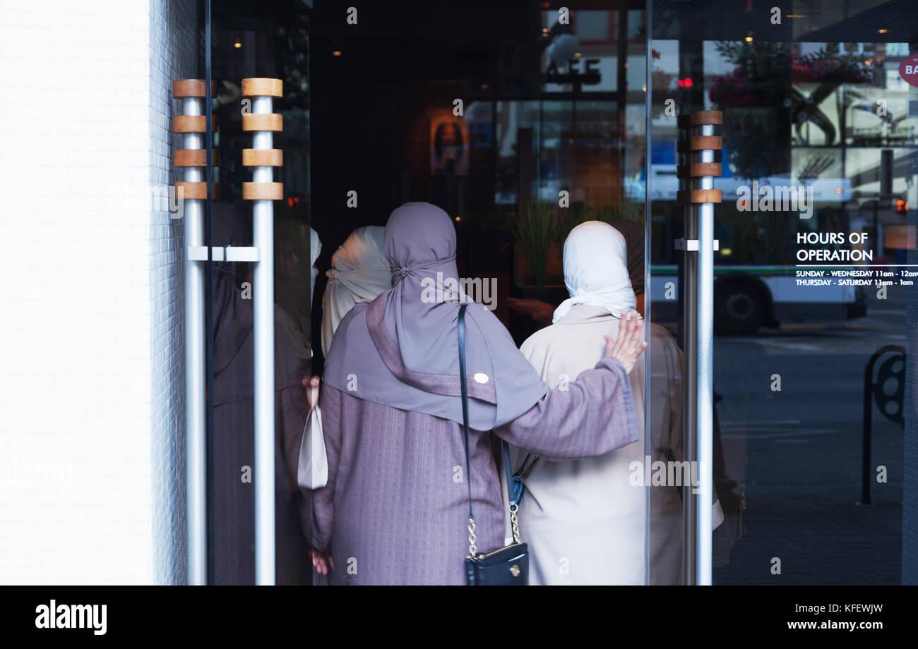 Muslim women entering restaurant, Victoria BC Canada - Stock Image