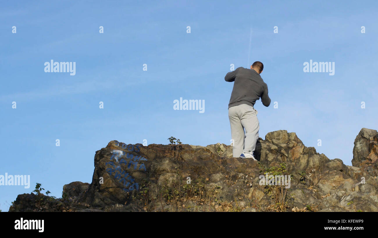 Silhouette of man boxing with shadow on the rock at sunset. Strong muscular boxer. Shadow fight on the rock. - Stock Image