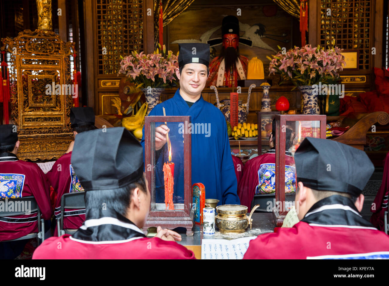 The monk lights a candle in one of the temple complexes in Shanghai city, China - Stock Image