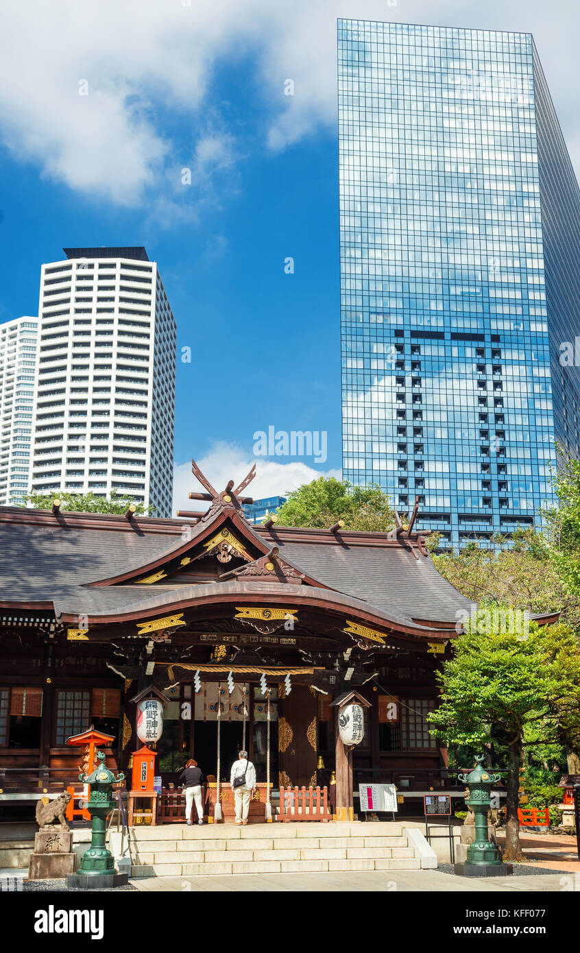 Tradition and Modernity in Japan. People pray in an old temple below modern skyscrapers in Tokyo. - Stock Image