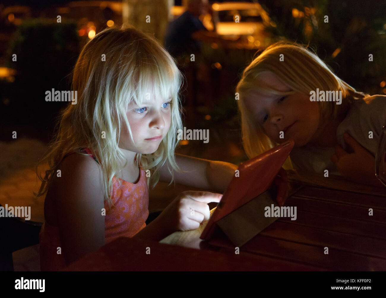 Girl tapping on here Ipad outside on a restaurant in evening when dark.  Here face is lit by the screen. Her friend - Stock Image