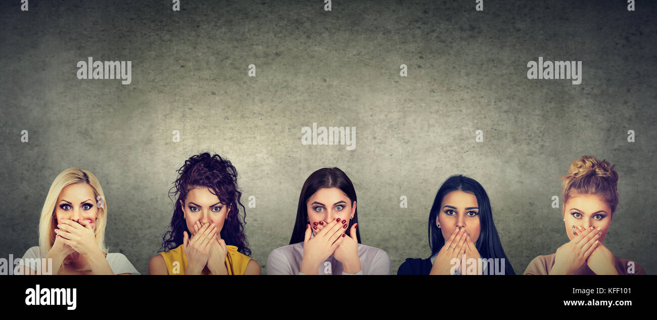 Group of multicultural women covering their mouth scared to speak out about abuse and domestic violence - Stock Image