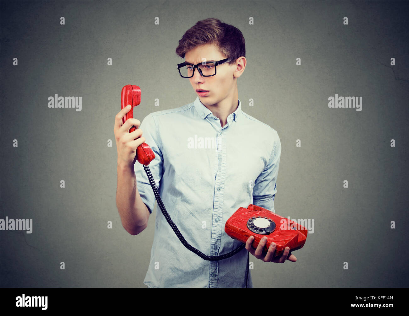 Confused teenager man looking at old fashioned telephone - Stock Image