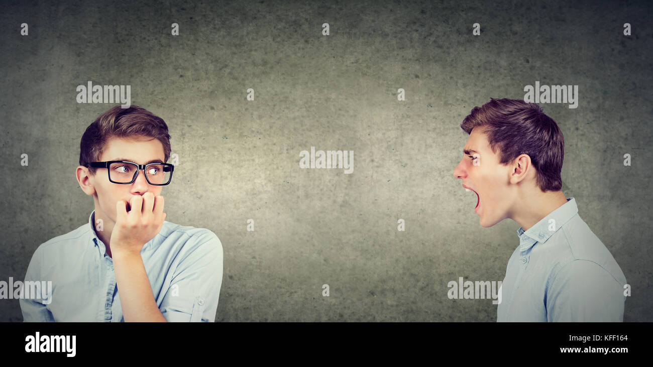 Split personality. Angry man screaming at scared anxious himself - Stock Image