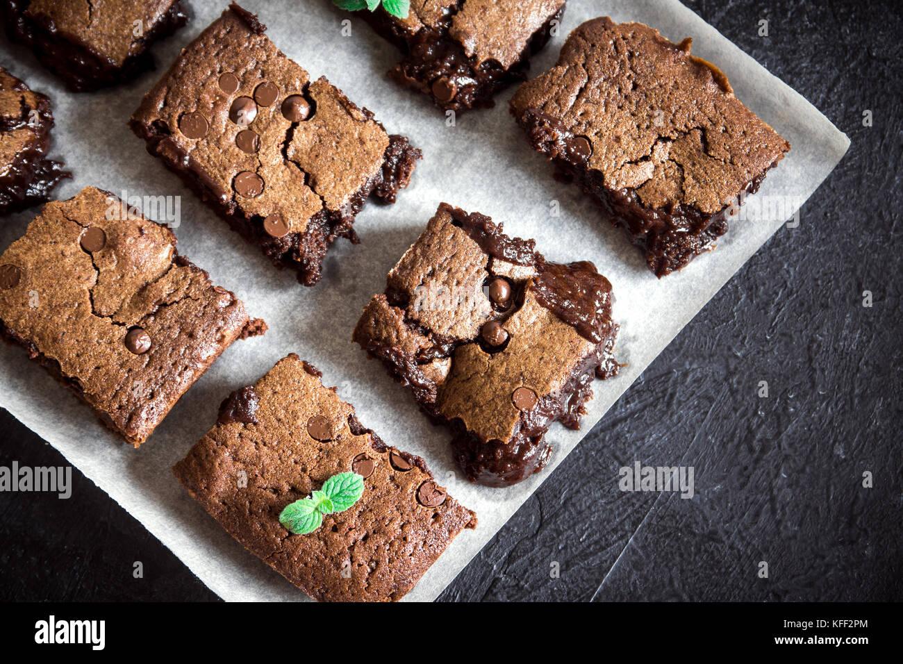 Brownies. Homemade chocolate fudge brownies on rustic black background, top view. - Stock Image