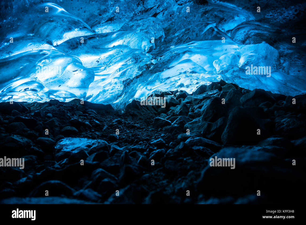 In a narrow tunnel under a glacier in British Columbia, Canada, the ice above glows blue from the sun shining through - Stock Image