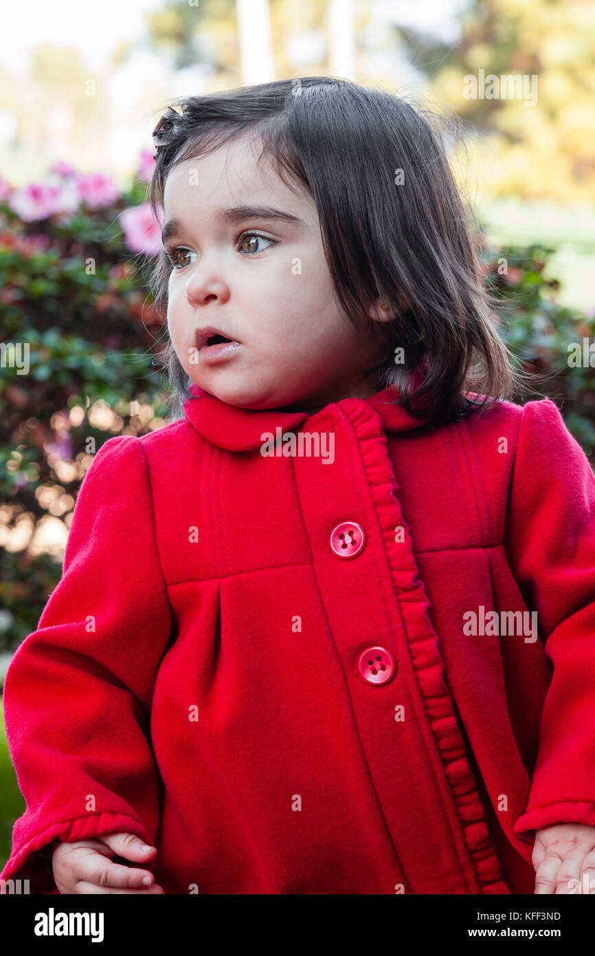 Cute, pretty, happy and fashionable toddler baby girl, wearing a good fashion red long coat or overcoat on cold - Stock Image