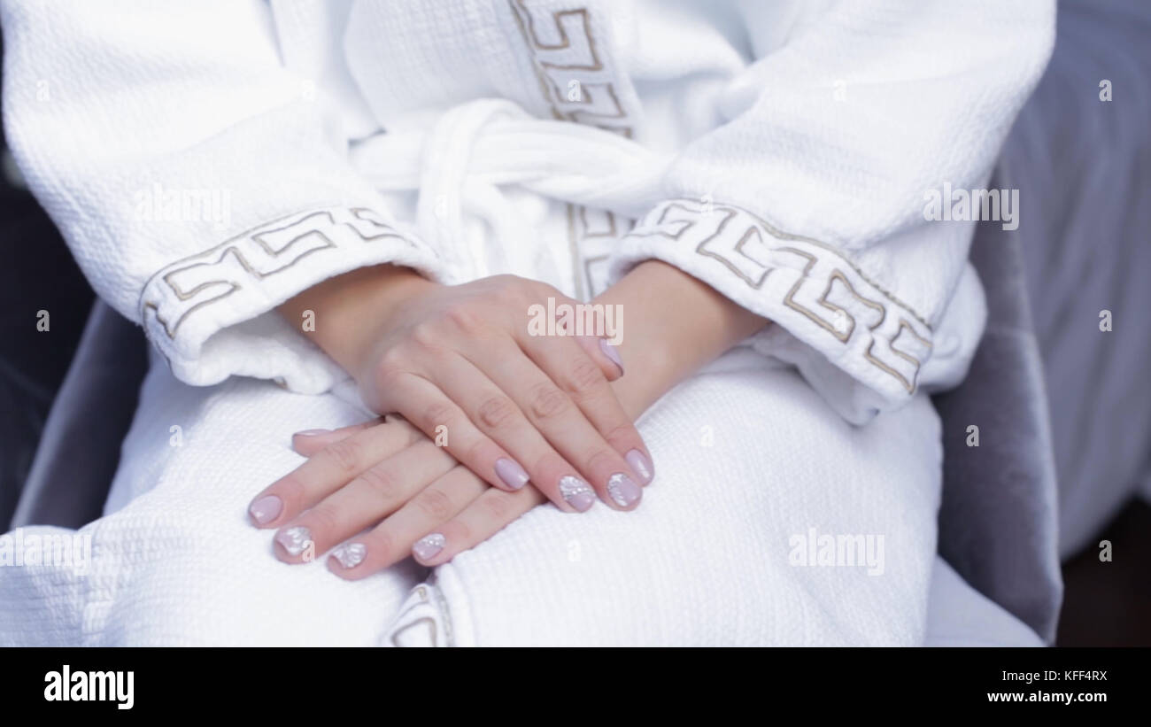 Bride sitting in a chair in white coat. woman sitting in woolen Bathrobe with flower. Bride preparing for wedding - Stock Image