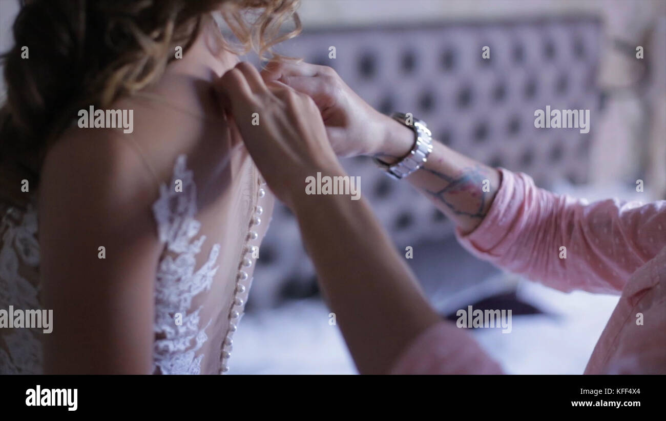 d26949fe5 Morning bride. maid of honor helping the bride with her dress. the bride's  lace