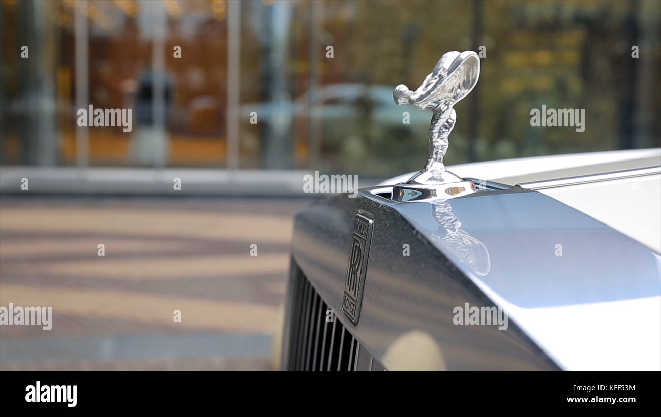 Spirit of Ecstacy or Emily logo on the hood of a rolls Royce. and bride the background. Emmy or Spirit of Ecstacy, - Stock Image