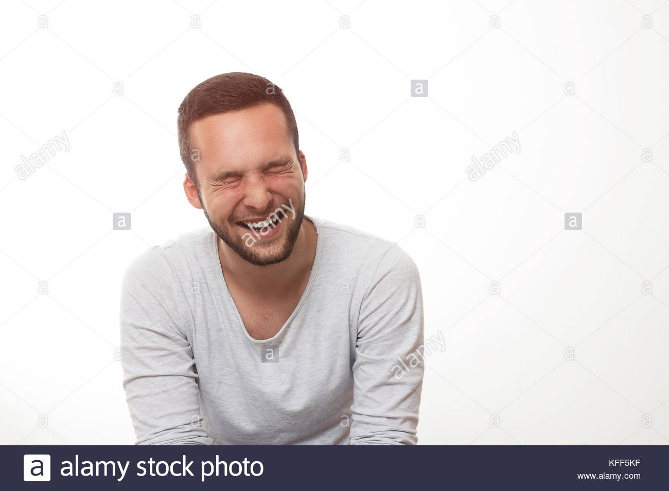 Young man smiling to the camera in the studio - Stock Image