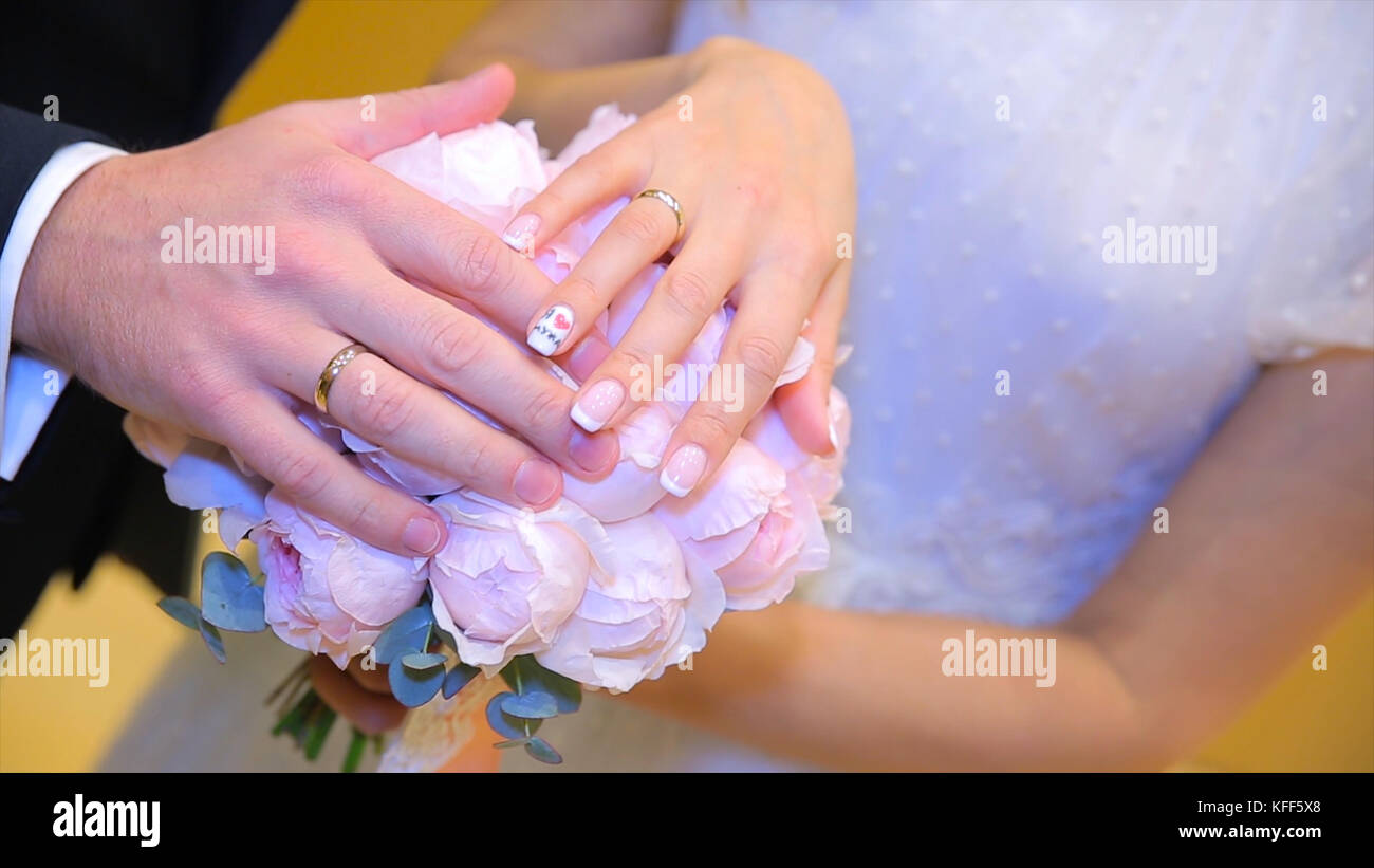 Newly wed couple\'s hands with wedding rings. Bride and groom with ...