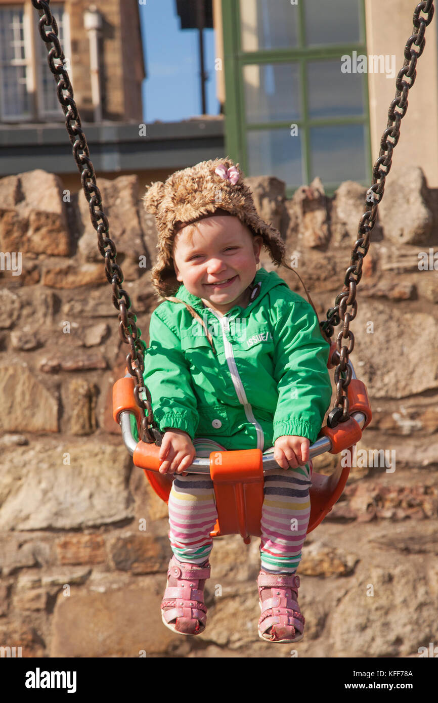 Smiling baby girl playing in children´s playground on Portobello Beach Promenade in capital of Scotland, in - Stock Image