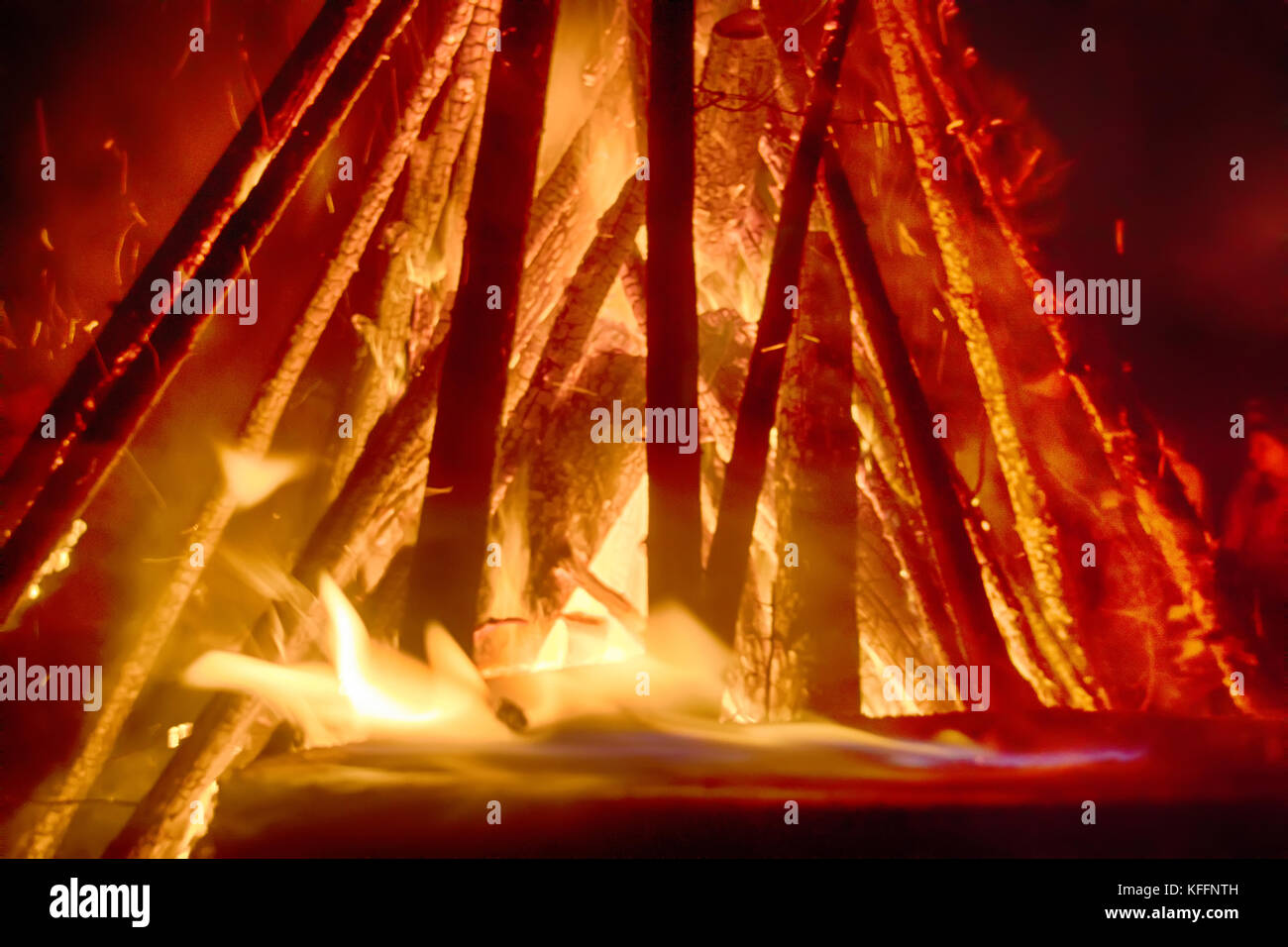 Huge fire at night and young people around. Pagan festival of Walpurgis night: bonfires, dancing wildly, demons, - Stock Image