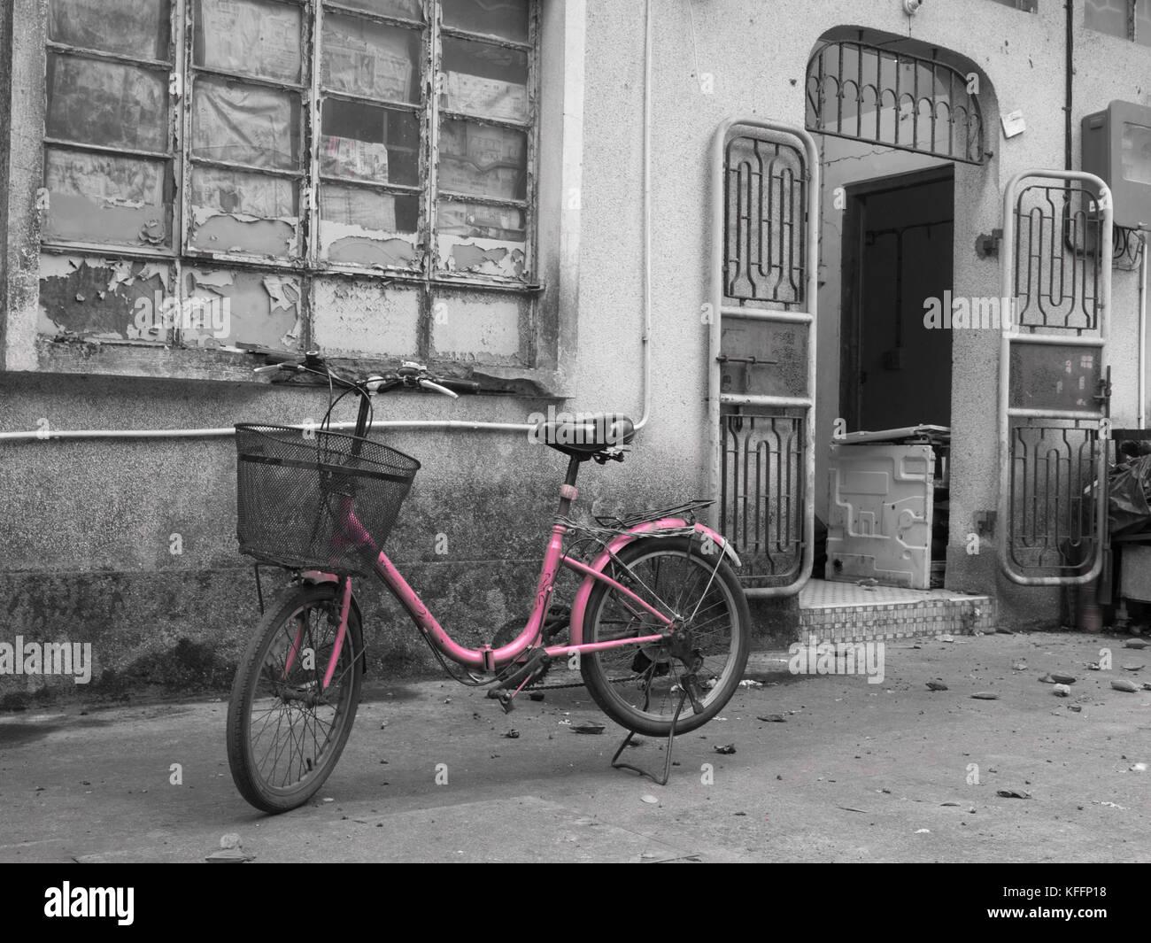 Pink Ladies bicycle outside premises at Tai O fishing village, Lantau Island, Hong Kong, China. - Stock Image
