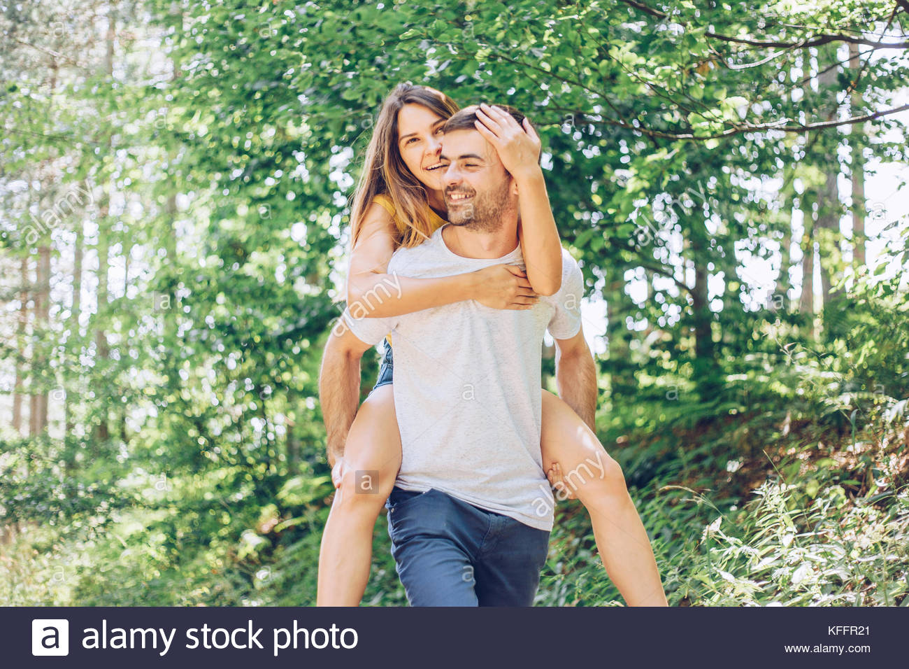Man carrying woman piggyback - Stock Image