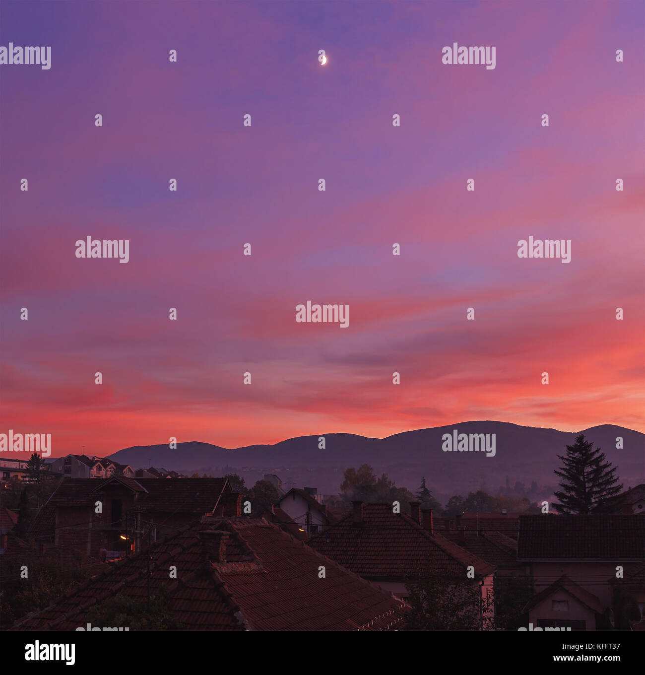 Sunset over small Balkan town, purple atmosphere and moon. - Stock Image