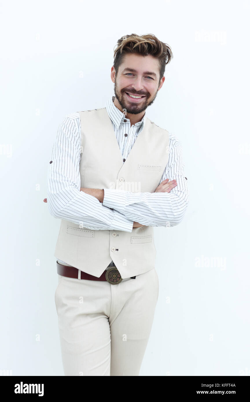 Portrait of a man in a suit with arms crossed, standing against a white wall - Stock Image