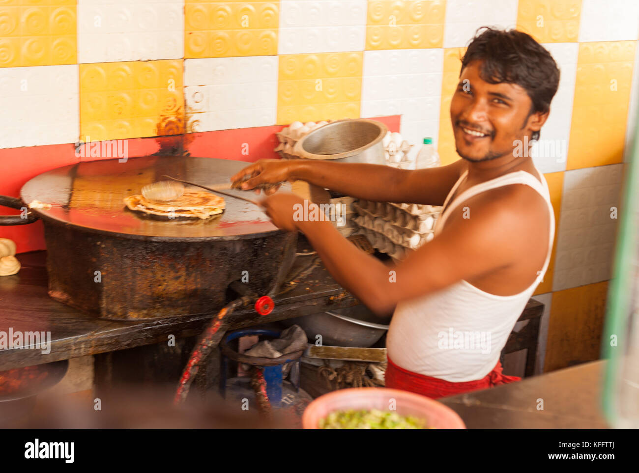 Kolkata street food vendor prepares a classic Bengali egg roll. - Stock Image