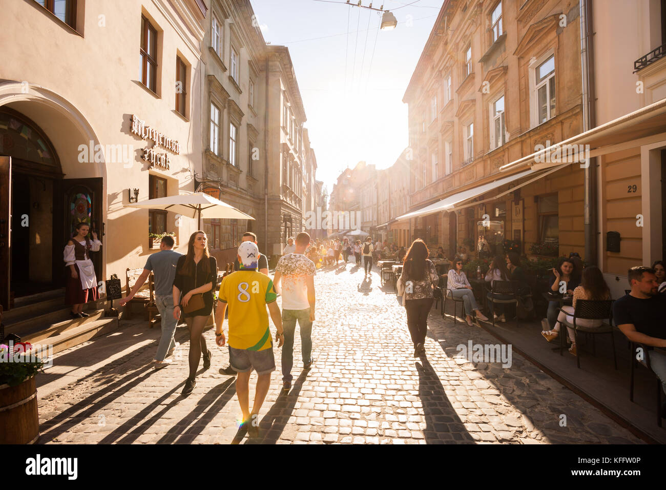 Tourists wander the cobblestone streets of the old city in Lviv, Ukraine - Stock Image