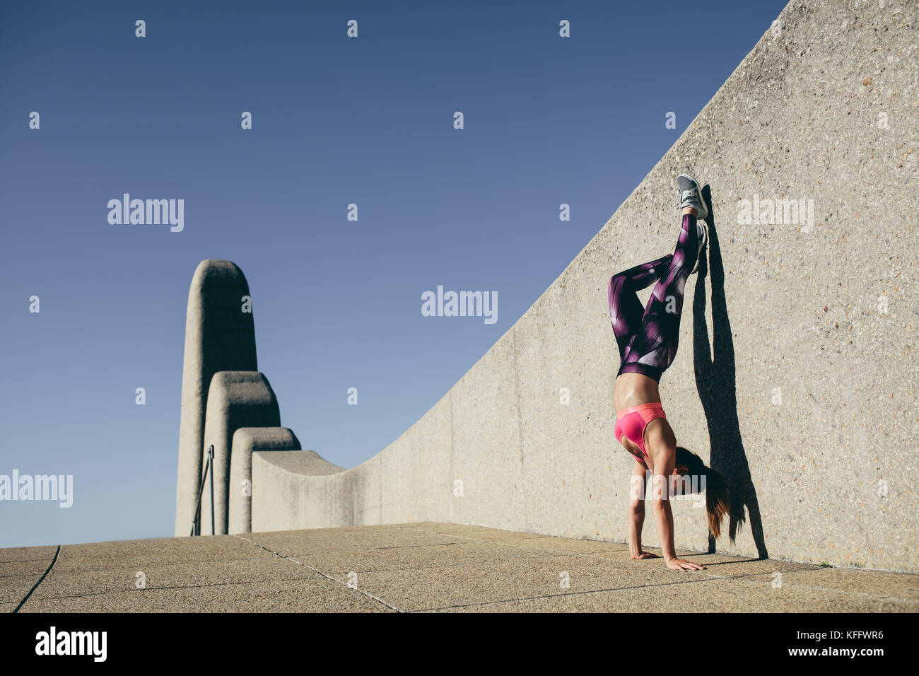 Physically fit woman doing hand stand outdoors. Healthy female standing on hands with feet lifted up against a wall. - Stock Image