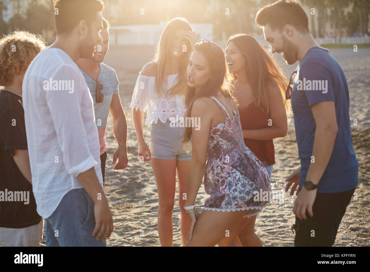 Portrait of group of happy friends partying on beach - Stock Image
