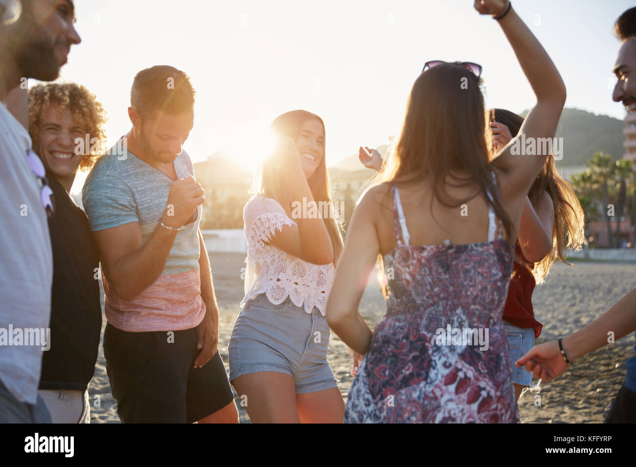 Portrait of young group of friends partying on beach - Stock Image