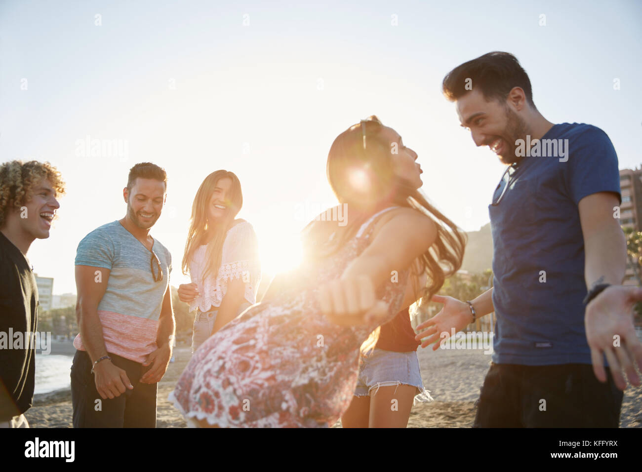 Portrait of couple dancing on beach partying with friends - Stock Image