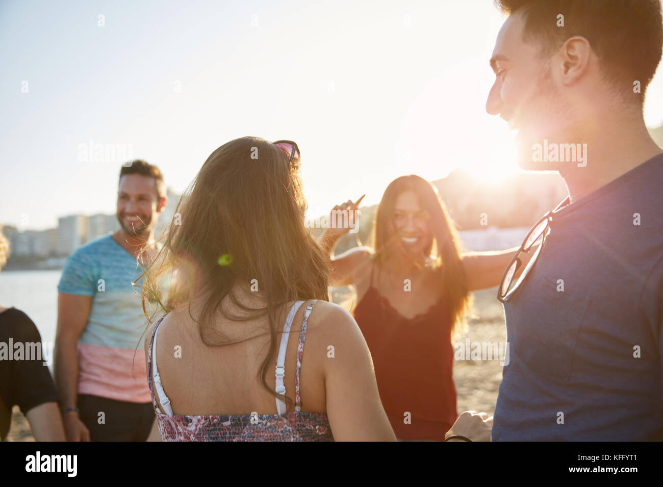 Portrait of happy group of friends dancing on beach - Stock Image
