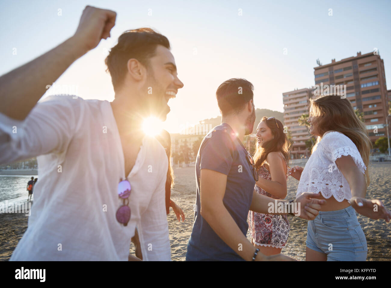 Portrait of young men dancing with their girlfriends on beach - Stock Image