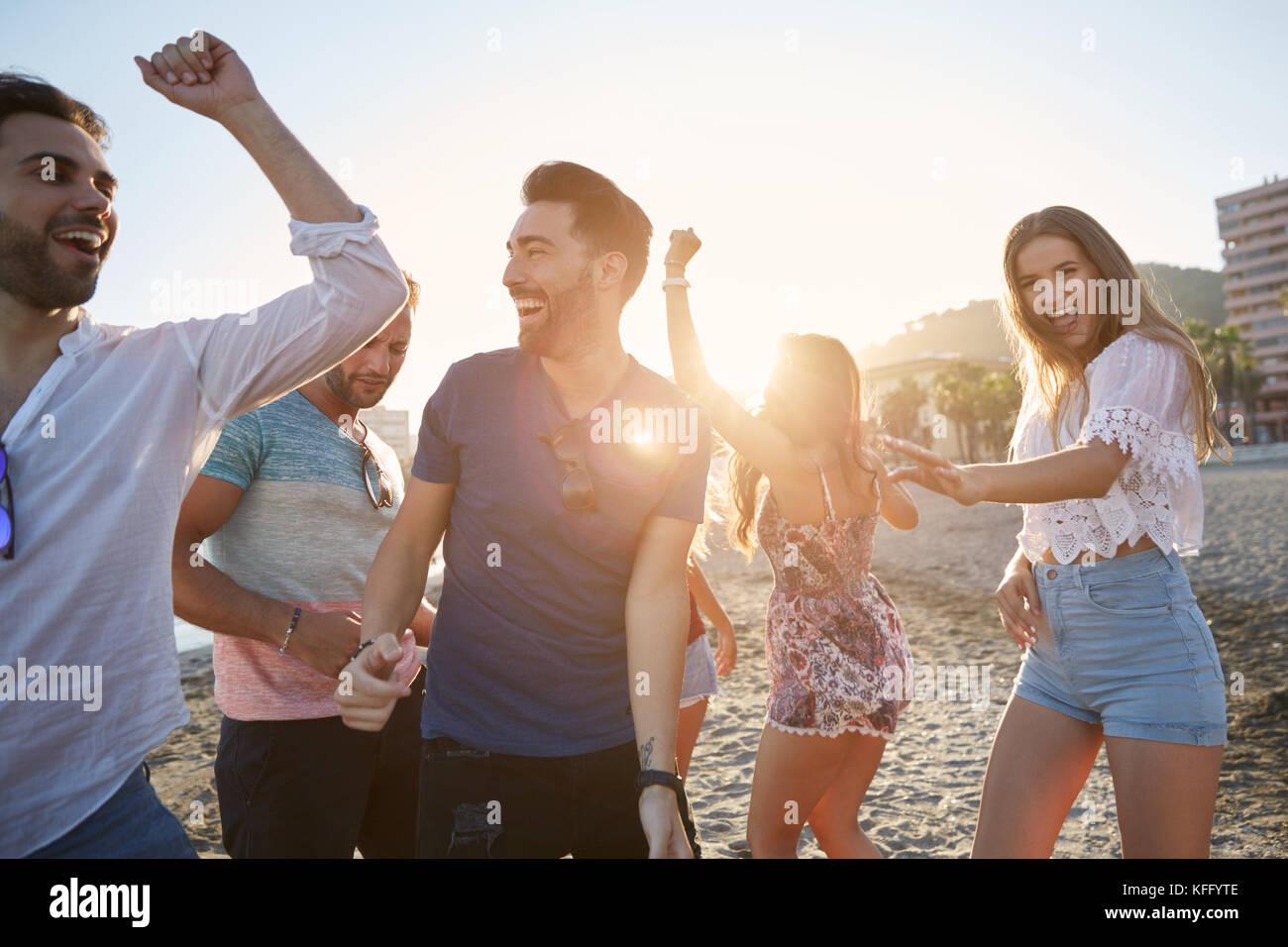 Portrait of young women dancing with their boyfriends on beach - Stock Image