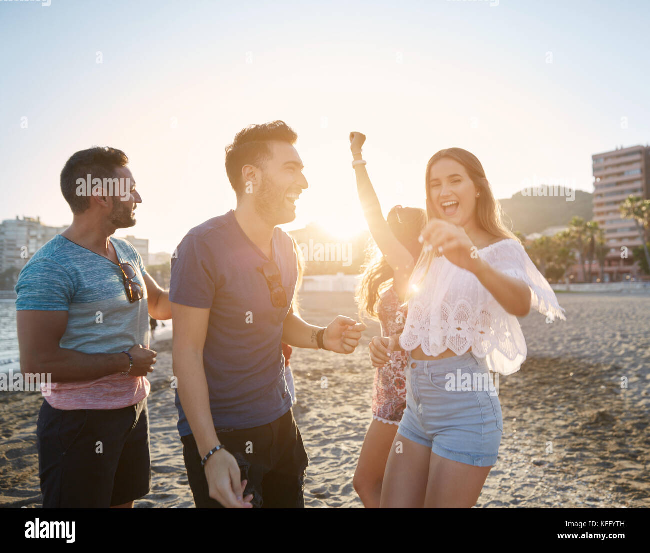 Portrait of young pretty woman dancing with friends on beach - Stock Image